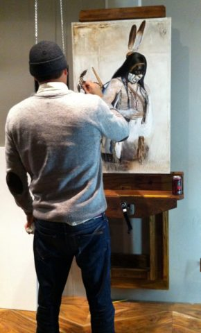 Photo of Ben McPherson painting a picture of an Apache indian
